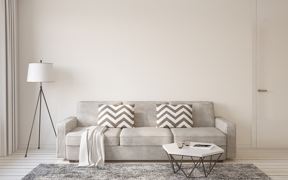 sala clara com sofá cinza neutro no meio