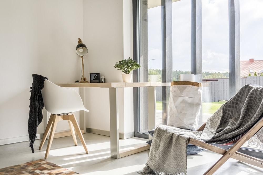 quarto com mesa e cadeira encostada em janela de vidro enorme